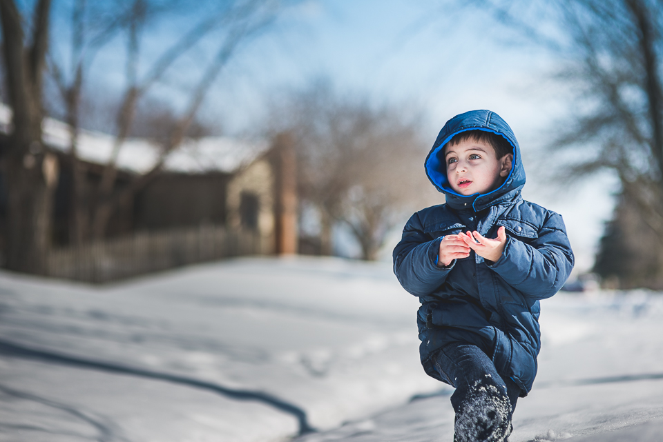 25 handsome boy in blue coat playing with snow