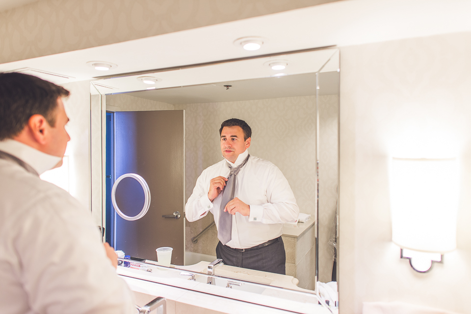 08 groom getting ready in mirror